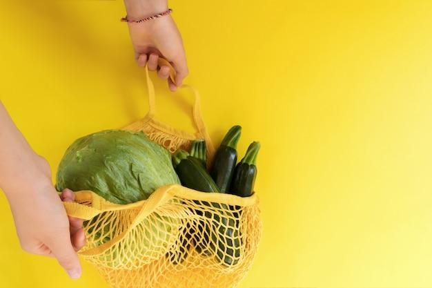 Vrouwenhand die een gele koord het winkelen zak met eco groene groenten houden