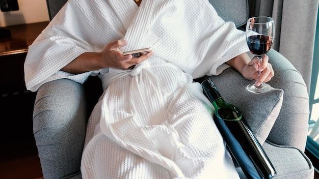 Vrouwenhand die een glas wijn en smartphone met wijnfles op de bank houden.