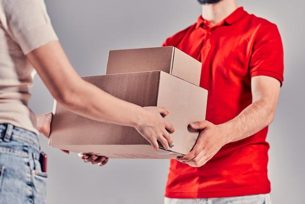 Vrouwenhand die een levering van dozen van bezorger accepteert.