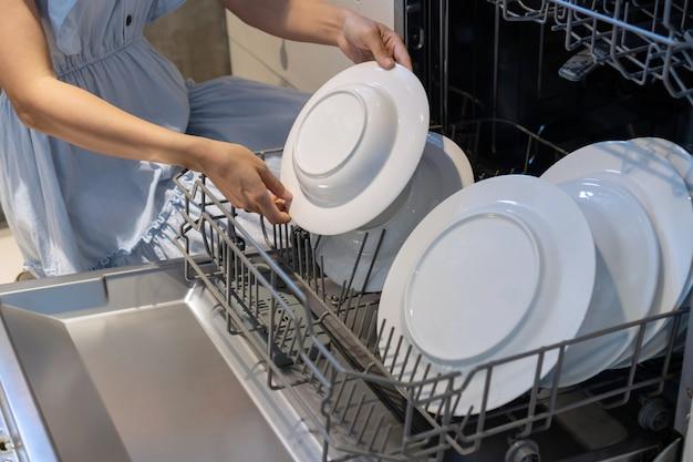 Vrouwenhand die een plaat in de afwasmachine zetten.