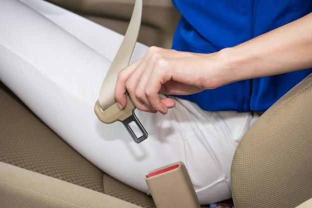 Vrouwenhand die een veiligheidsgordel in de auto vastmaken