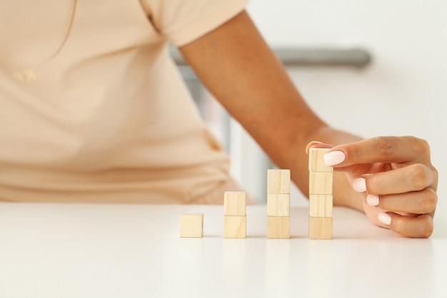 Vrouwenhand die en lege houten kubussen op bureau zetten en stapelen