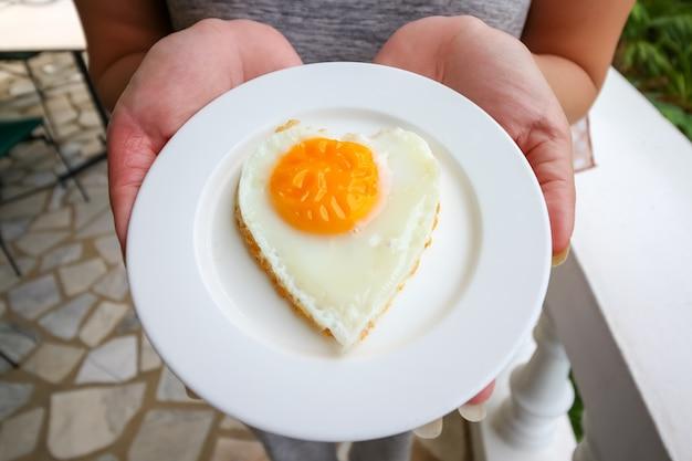 Vrouwenhand die gebraden eieren in ideaal hart op de witte plaat houden
