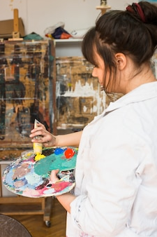 Vrouwenhand die gele verfbuis op slordig het schilderen palet drukken