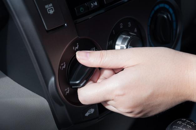 Vrouwenhand die het systeem van de autoairconditioning aanzetten