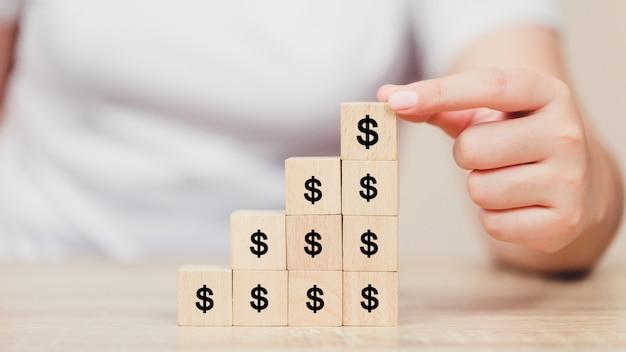 Vrouwenhand die houtsnede met de dollar van het pictogramgeld, de groei, financiën en investeringsconcept schikken.