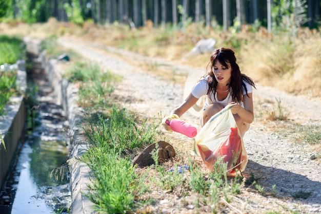 Vrouwenhand die huisvuil van het gras in het platteland verzamelen