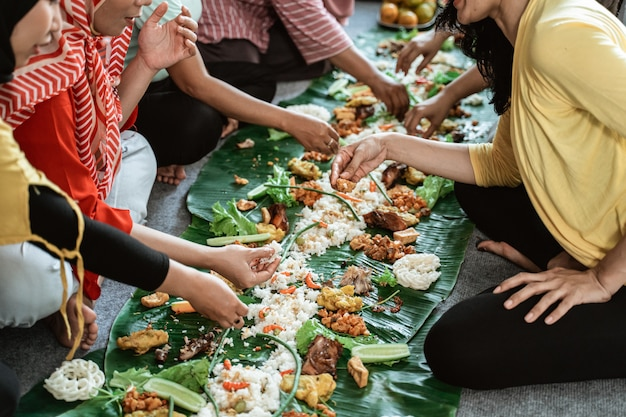 Vrouwenhand die hun voedsel eten die samen op banaanblad leggen