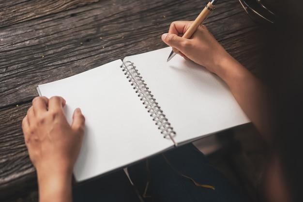 Vrouwenhand die in klein wit memorandumnotitieboekje neerschrijven voor neemt een nota om niet te vergeten of lijstplan te doen.
