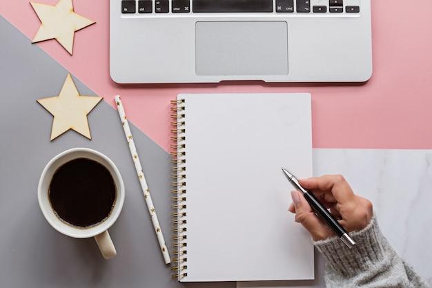 Vrouwenhand die in notitieboekje schrijven