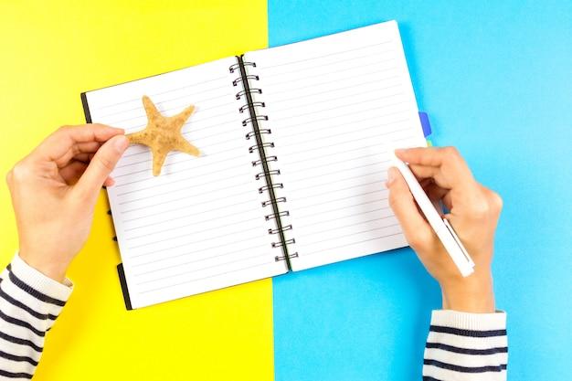 Vrouwenhand die in open reisnotitieboekje schrijven over blauwe en gele achtergrond