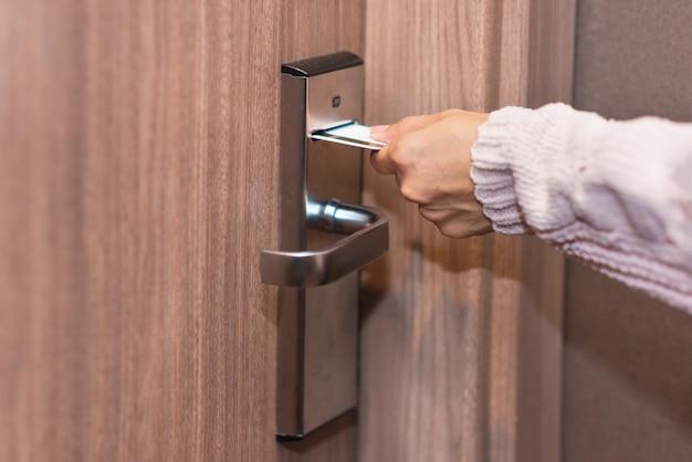 Vrouwenhand die kaart opnemen om elektronisch slot in hoteldeur te openen