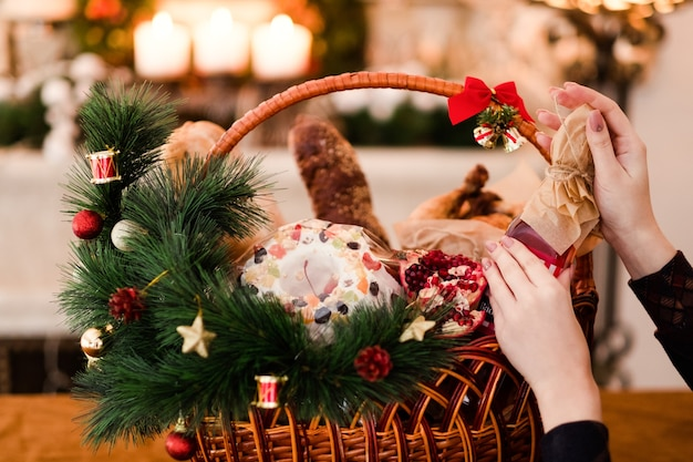 Vrouwenhand die kerstmisgoederen in een mand schikken. feestelijke vakantie voedsel cadeau concept