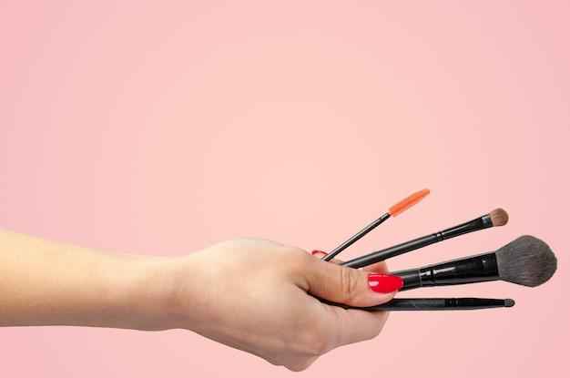 Vrouwenhand die kosmetisch hulpmiddel houden dat op kleur wordt geïsoleerd