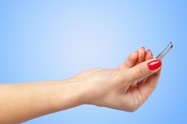 Vrouwenhand die kosmetisch hulpmiddel houden dat op kleurenachtergrond wordt geïsoleerd