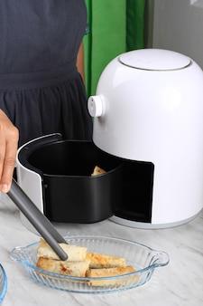 Vrouwenhand die lumpia uit airfryer haalt, zelfgemaakte knapperige zoete lumpia maakt met airfryer, gezonde stule-snack zonder olie. elektrische keukengadget voor vetvrij dieet