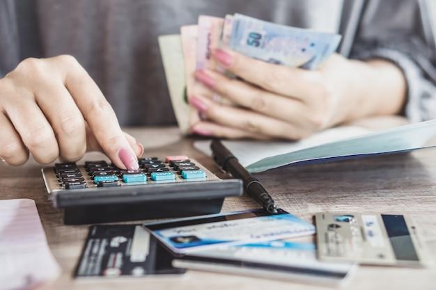Vrouwenhand die maandelijkse uitgaven voor creditcard berekenen