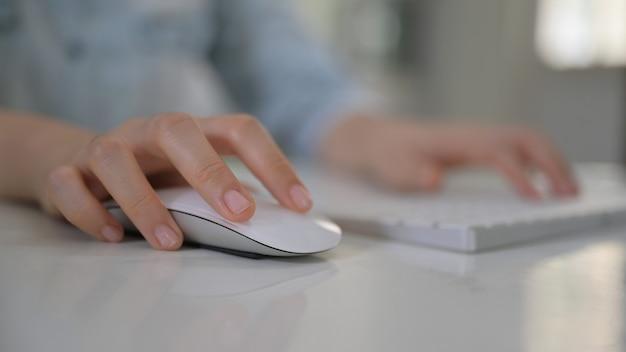 Vrouwenhand die muis en computertoetsenbord gebruiken.