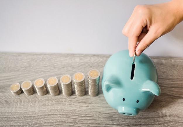 Vrouwenhand die muntstuk in blauw spaarvarken stopt met de groeigrafiek van de muntstapel, geld besparen voor toekomstig investeringsplan en pensioenfondsconcept