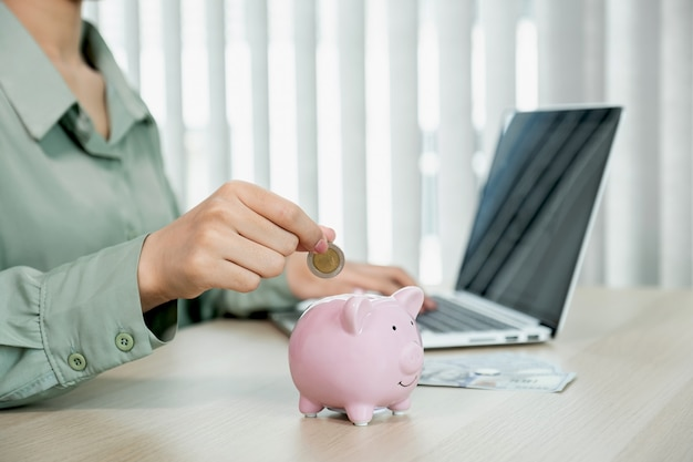 Vrouwenhand die muntstuk in spaarvarken stopt, geld bespaart voor toekomstig plan en pensioenfondsconcept.