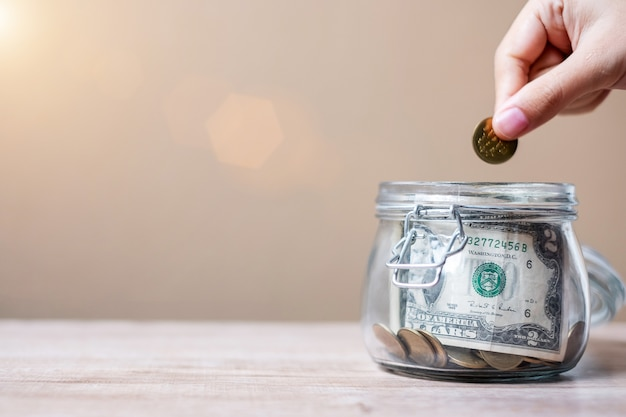 Vrouwenhand die muntstukgeld in glaskruik zetten. wereldspaardag, zakelijk