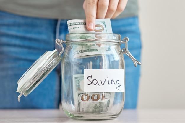 Vrouwenhand die ons dollarrekening houden en glaskruik met inschrijvingsbesparing aanbrengen. geld besparen en huisbegroting concept