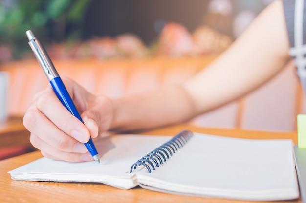 Vrouwenhand die op een blocnote met een pen in het bureau schrijven.