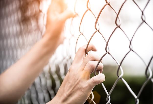 Vrouwenhand die op kettingslink omheining houden voor de mensenrechtendag