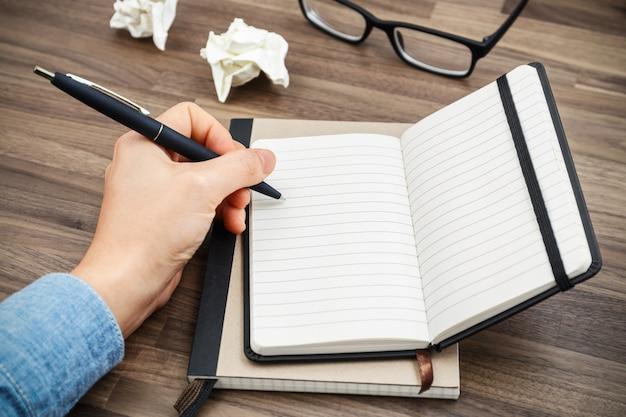 Vrouwenhand die op notitieboekje schrijven