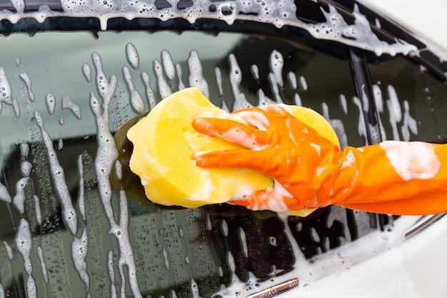 Vrouwenhand die oranje handschoenen met gele spons dragen die zijspiegel moderne auto wassen