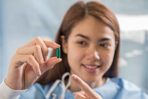 Vrouwenhand die pillen houdt neemt geneeskunde volgens de orde van de arts