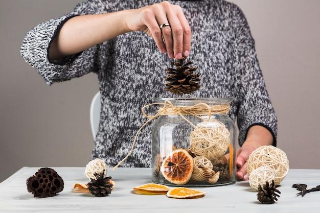Vrouwenhand die pinecone in glaskruik zetten