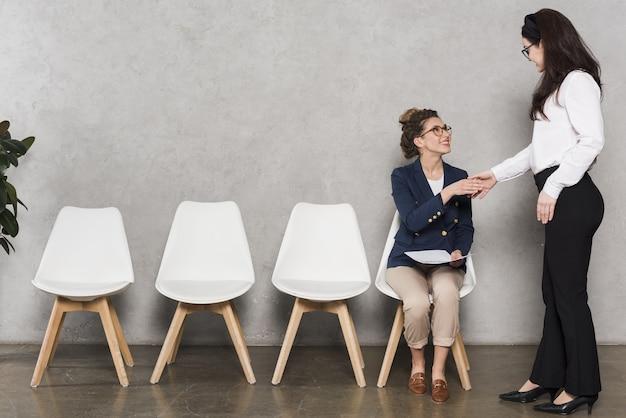 Vrouwenhand die potentiële werknemer schudden vóór baangesprek