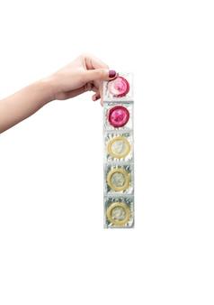 Vrouwenhand die rij van verzegelde condooms tonen