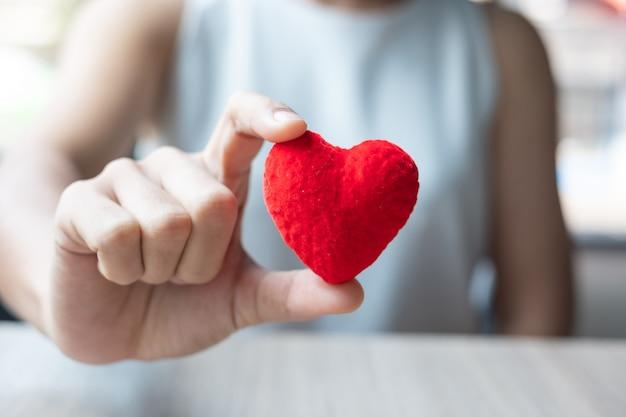Vrouwenhand die rode hartvorm houden