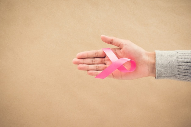 Vrouwenhand die satijn roze lintcampagne geeft in oktober,