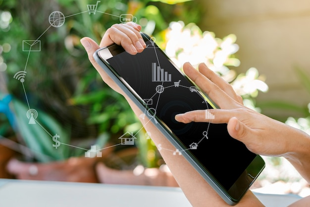 Vrouwenhand die tablet met vage sociale media en technologiepictogrammen houdt.