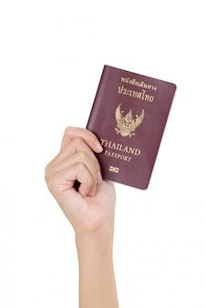 Vrouwenhand die thais die paspoort houden op wit wordt geïsoleerd