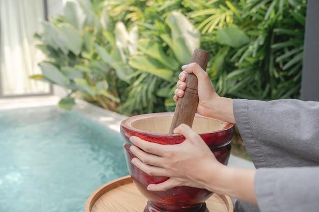 Vrouwenhand die thais eten maakt, roept papajasalade of som tam, mengen en stampen in een vijzel