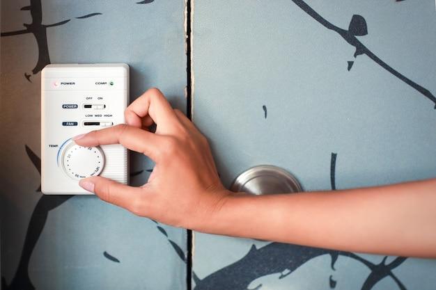 Vrouwenhand die thermostaat gebruiken