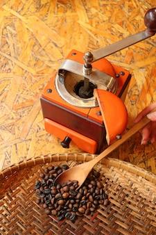 Vrouwenhand die tot geroosterde koffiebonen met houten lepel tot een kom vormen