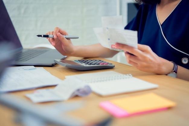 Vrouwenhand die uitgavenrekening en berekening over schuldrekeningen maandelijks bij de lijst in huisbureau houden.