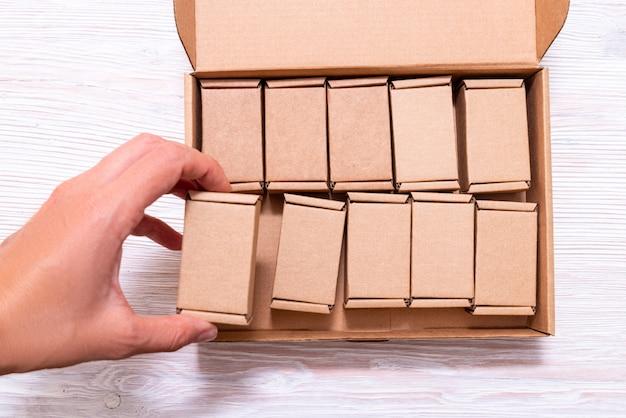Vrouwenhand die veel kleine kartondozen binnen van grote geval met dekking zetten