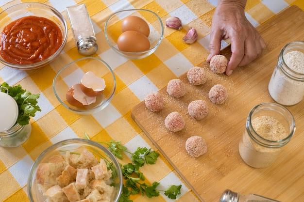 Vrouwenhand die verse gehaktballen klaarmaakt om te worden gekookt, houten snijplank en rauwe ingrediënten