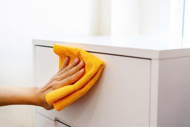 Vrouwenhand die wit kabinet met oranje kleur microfiber doek thuis in slaapkamer schoonmaken. concept van het desinfecteren van oppervlakken tegen bacteriën of virussen. detailopname