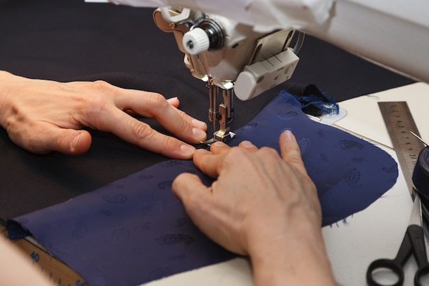 Vrouwenhand die witte doek door een naaimachine leiden
