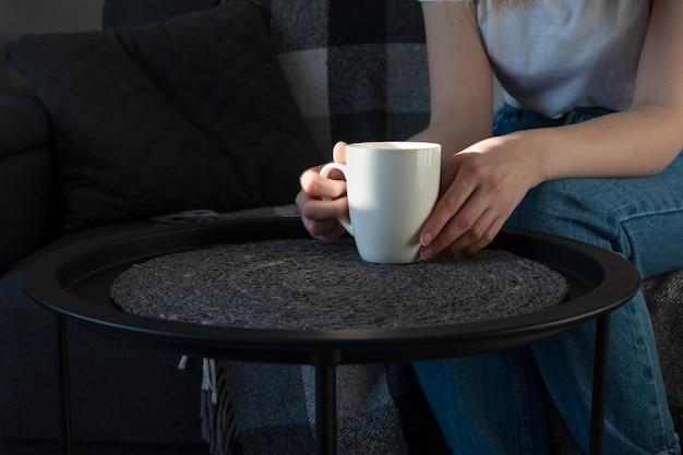Vrouwenhand die witte kop op koffietafel op bank in zonnige dag houden, binnen. rust thuis, levensstijl.