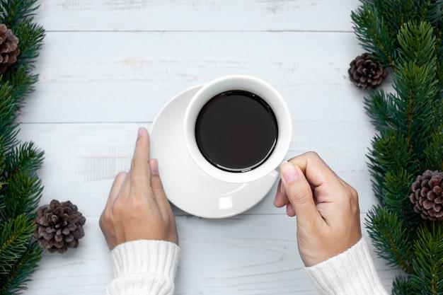 Vrouwenhand die zwarte koffiekop met kerstmisdecoratie, gelukkig nieuwjaar en kerstmisvakantie houden
