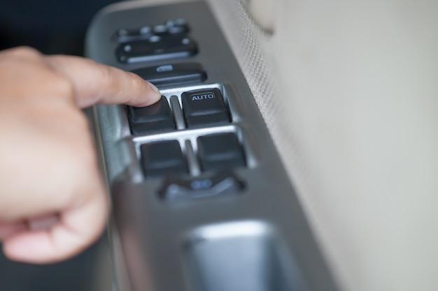 Vrouwenhand dringende knoop controlerend venster in de auto