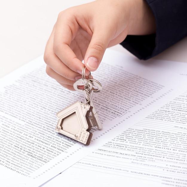 Vrouwenhand en huissleutel, ondertekend contract en sleutels van het bezit met documenten.